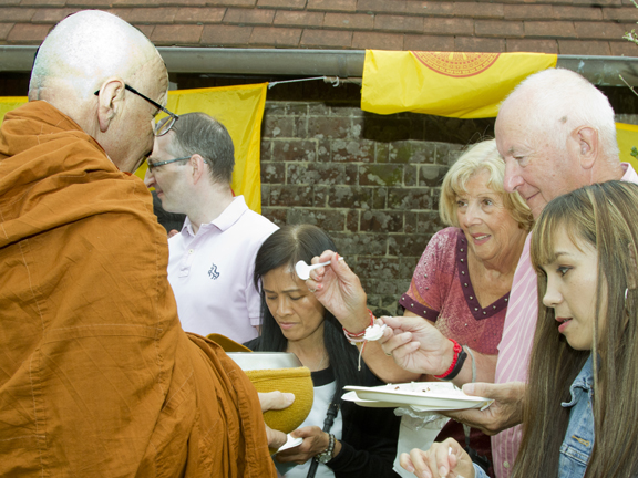 Monks pass along the line of guests offering them rice.